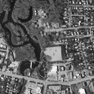 A Featureless Square Marks The Spot Of An Abandoned Parking Lot, Flanked By The Winding Ashuelot River.